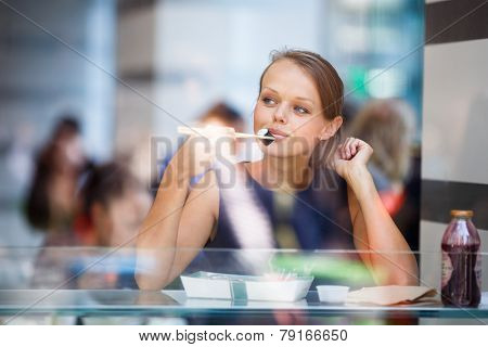 Pretty, young womna eating sushi in a restaurant, haivng her lunch break, enjoying the food, pausing for a while from her busy corporate/office life (color toned image)