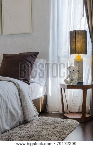 Brown Pillow On Bed With Wooden Table And Lamp