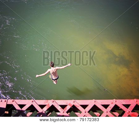 a boy jumping of an old train trestle bridge into a river
