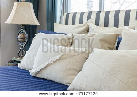 Pillows On Blue Bed With Lamp