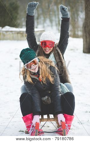 Laughing girls sledge downhill in wintertime enjoy snow