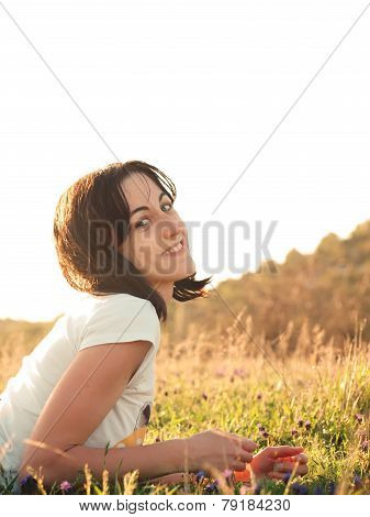 Girl lying in a field of flowers and smiling.
