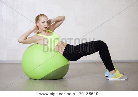 Woman in a gym training with fitness ball
