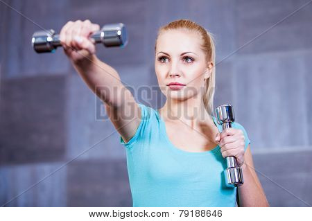 Strong young woman exercising with dumbbells at the gym