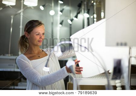 Pretty, young woman choosing the right light for her apartment in a modern home furnishings store (color toned image; shallow DOF)