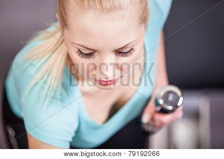 Attractive blonde sports girl lifting dumbbell doing workout in a fitness club or gym