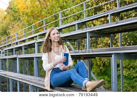 Student Sitting On Sport Tribune With Book And Smiling At Camera