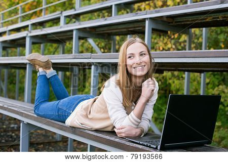Student Lying On Sport Tribune Smiling And Looking Away