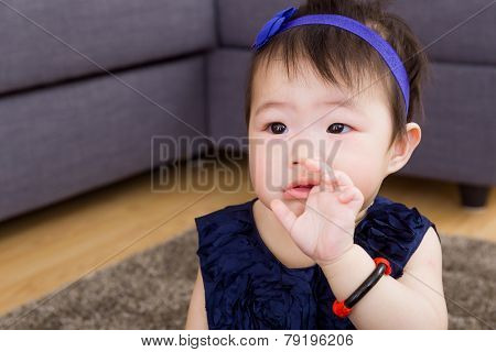 Baby girl sucking finger with navy blue dressing