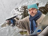 stock photo of ice-scraper  - The mid adult man cleans a frozen windshield - JPG