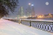 foto of windy  - Embankment and business center view at cold windy evening time - JPG