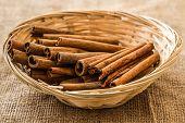 picture of cinnamon sticks  - Cinnamon sticks in straw basket on a linen napkin - JPG