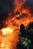 stock photo of firefighter  - Two firefighters at a fire fighting exercise in a container - JPG