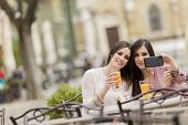 stock photo of cafe  - Young women taking photo with cellphone in the cafe - JPG