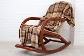 pic of floor covering  - Rocking chair covered with plaid on wooden floor near the brick wall background - JPG