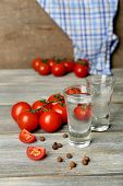 stock photo of ouzo  - Glasses of ouzo and tomatoes on wooden table - JPG