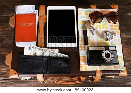 Packed suitcase of vacation items on wooden table, closeup