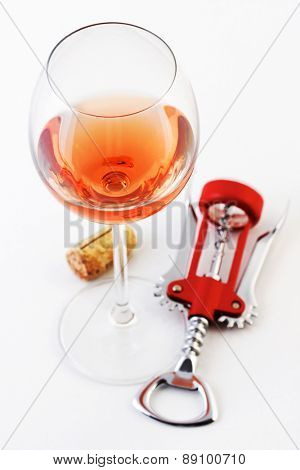 Glass of rose wine and corkscrew
