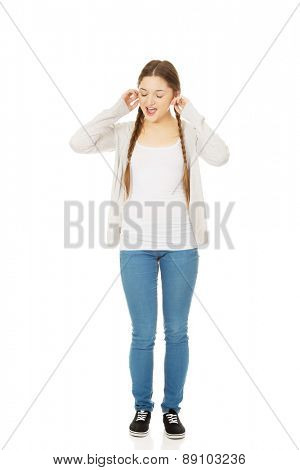Angry teen woman covering ears with fingers.