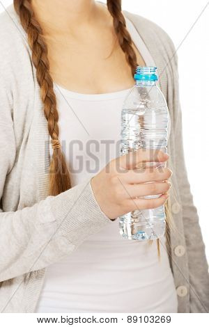 Teenage woman with bottle of mineral water.