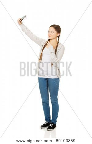 Happy teen woman taking selfies with smart phone.