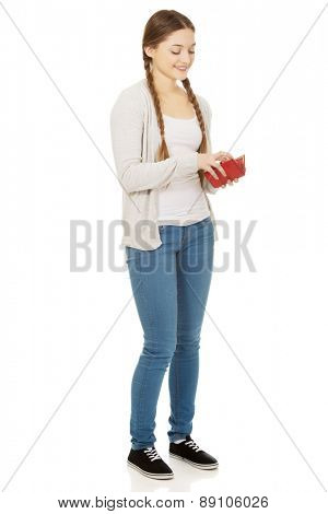 Happy beautiful teen woman with a wallet.