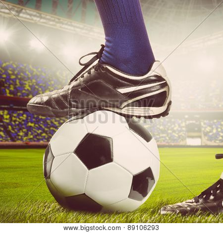 legs of a soccer or football player on ball on stadium, warm colors toned