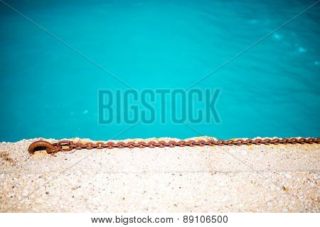 Rusty chain on the concrete with water