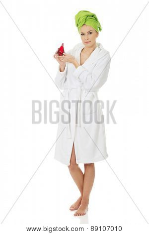 Woman in towel turban with bottle of parfume.