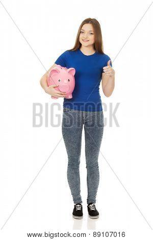 Teenage woman with piggybank and thumbs up.