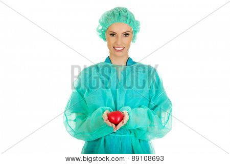 Smiling female surgeon doctor with heart.