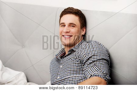 Handsome young smiling man sitting in bedroom.