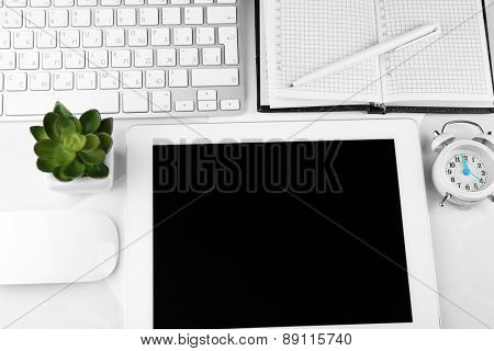 Office workplace with tablet and pot plant close up