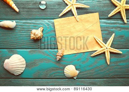 Card blank with sea stars and shells on wooden background