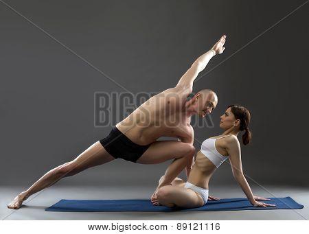 Studio shot of paired yoga, on gray background