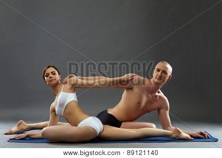 People practicing yoga in pair posing at camera