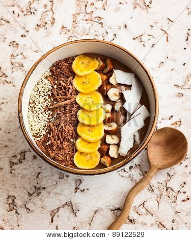 Chocolate hazelnut smoothie bowl topped with sliced banana, shredded coconut, chopped  chocolate, nuts and sesame seeds.