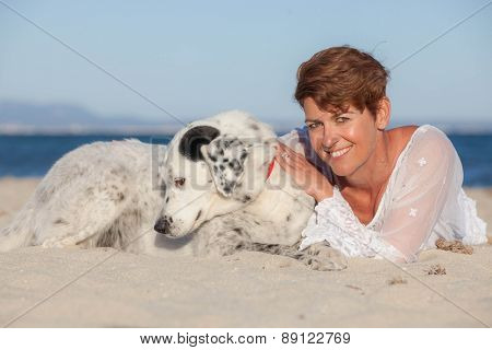 woman laying on beach on vacation with pet dog