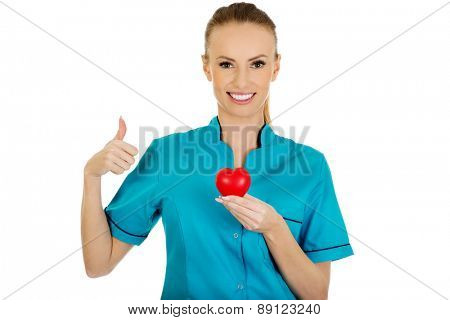 Smiling female doctor with heart and thumbs up.