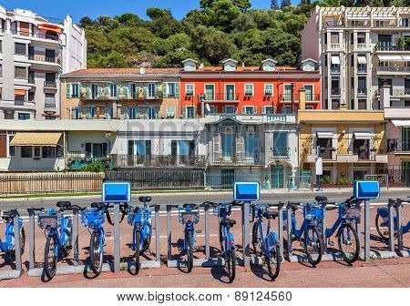 City bicycles at sharing station and colorful houses on background in Nice, France.