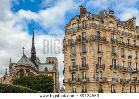 View on typical parisian building as Notre Dame de Paris Cathedral on background.