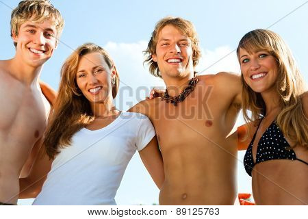 Group of four very beautiful people - men and women - on the beach
