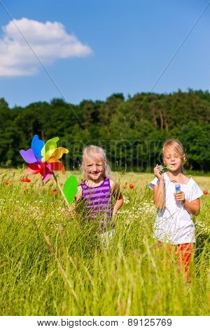Two children in field playing with soap bubbles and windmill