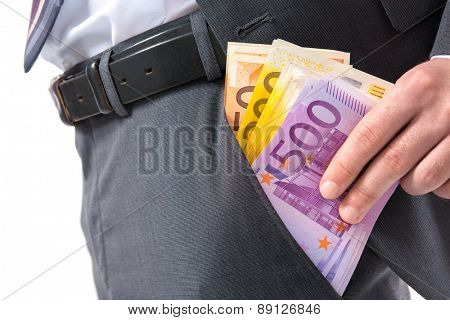 A businessman in a suit putting money in his pants pocket
