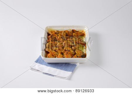 baked chicken wings in marinade, served in the tray