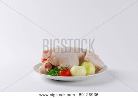 side view of whole raw chicken with fresh tomato and peeled onion