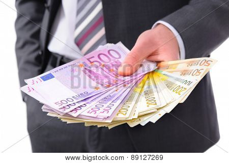 Businessman holding many euros banknotes