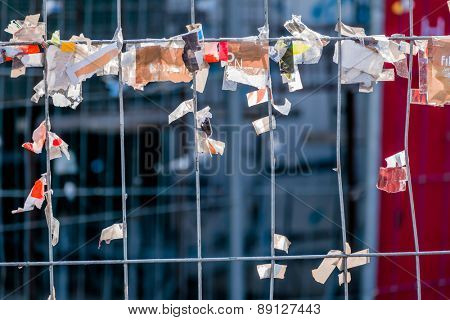 scraps of paper against a wire fence, symbolizing creativity, disorder and protest,