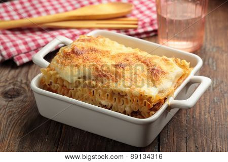 Lasagna bolognese in a baking dish on a rustic table