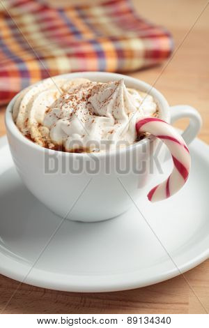 Cup of coffee with whipped cream, candy cane, and cinnamon